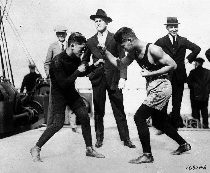 Pancho Villa spars with a stablemate as Frank Churchill watches on