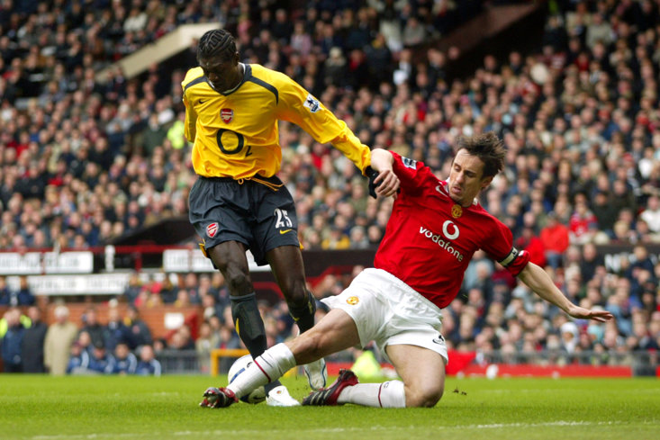 Manchester United's Gary Neville slides in to tackle Arsenal's Emmanuel Adebayor