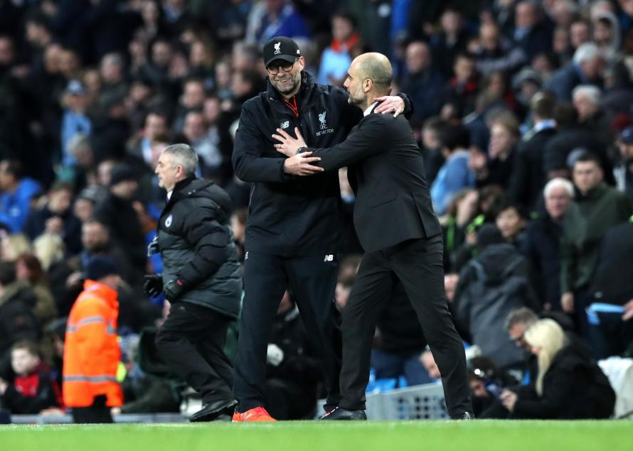 Jurgen Klopp and Pep Guardiola share a moment on the touchline