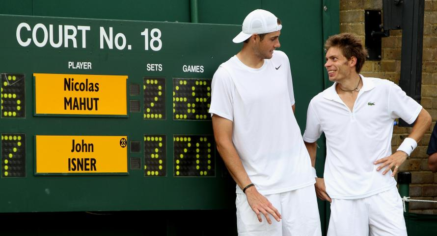 John Isner celebrates victory over Nicolas Mahut (right) as they stand by the scoreboard, in their record-breaking match on Court 18 during Day Four of the 2010 Wimbledon Championships